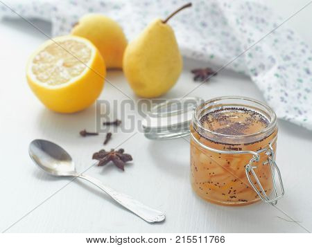 Pear jam in a jar with napkin upon white wooden table. Selective focus on the jar.