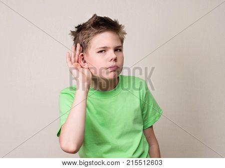 Human face expression emotion body language. Curious preteen boy listens. Closeup portrait child hearing something parents talk gossips hand to ear gesture. poster