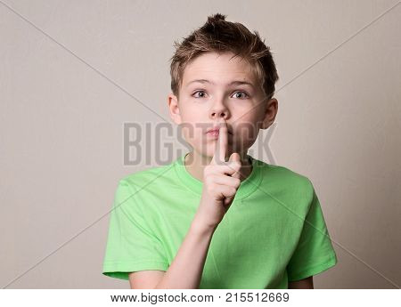 Scared boy doing a silence gesture. Kid putting finger up to lips and ask silence.