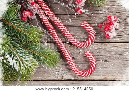 Christmas candy cane and snow fir tree on wooden table. Top view