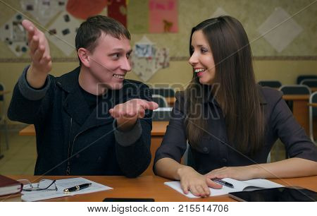 Lesson. Lecture. Teacher explain to his student a school material. Two students sits at school desk table in a classroom and one explain topic to the other.