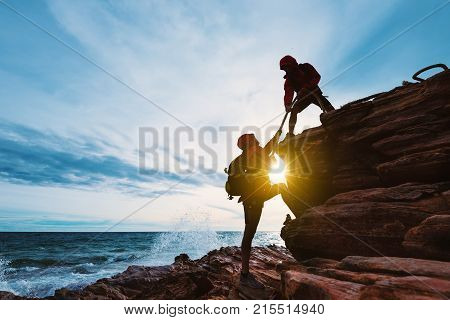 Young asian couple climbing up on the mountain,giving helping hands,support togethers,support,hiking and team work concept.