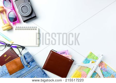 Travel Planning accessories Airplanewallet sun glasses money note pad jeans action cameraworld map and passport with blank space on white background. for Traveling prepare concept flat lay.