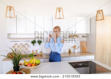 Charming woman walks up and goes to kitchen table, raises hands to sides and up to relieve tension and takes in hands fragrant morning fresh coffee, smiles with easy smile, standing in middle of stylish and white kitchen with variety of cooking appliances