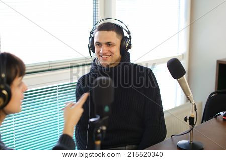 Cute female radio host and funny guy with headphones and talking are direct inclusion of radio, sitting in chair in radio studio. In office ponoramic large windows on desktop are microphones and mixing consoles, broadcast processor