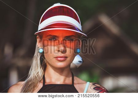 Portrait of a beautiful girl in a red visor closeup. Wearing Large turquoise earrings. Holiday in Thailand.