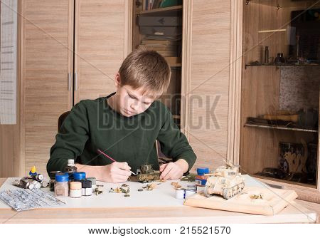 Hobby and leisure concept. Teen boy assembling and painting plastic model tank at workplace in his room.