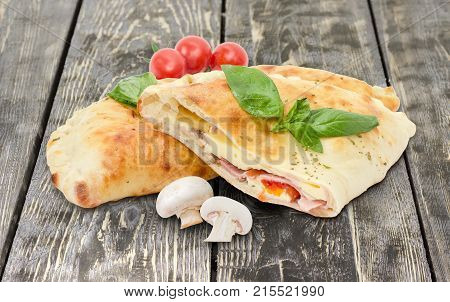 Half and whole of the baked calzone - closed type of pizza that is folded in half decorated with basil twigs raw mushrooms and cherry tomatoes on an old rustic wooden surface