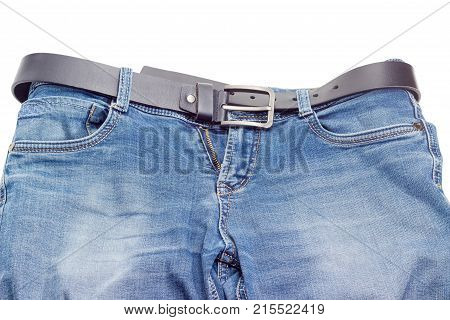 Casual black belt for men made of thick leather with classical buckle passed through the belt loops of the blue jeans on a white background