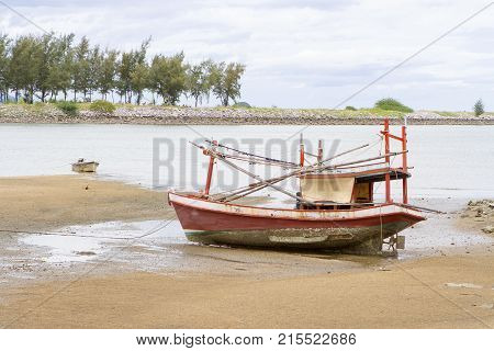 Fishing boats the  old red run aground of day ligth