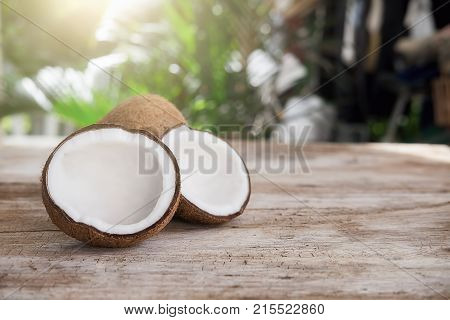Ripe half cut coconut on a wooden background. Coconut cream and oil.