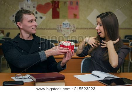Young man student confesses love to his girl classmate and gives her a gift in a box. School love concept.