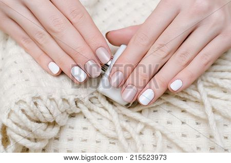 Female hands with white nail design holding nail polish bottle.