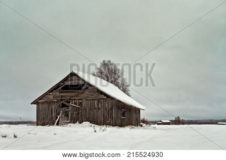Old barn houses on the snowy fields of the Northern Finland. The snow has covered everything on a cold winter day.