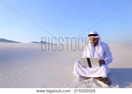 Successful young businessman male Muslim uses laptop to build drawing in Photoshop and prints fingers on laptop sitting on white sand in bottomless wide desert in afternoon against blue sky. Swarthy Muslim with short dark hair dressed in kandura, long, sp