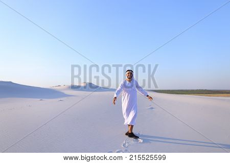 Successful Muslim tourist guy smiles broadly and spreads hands to sides and whirls around, laughs and smiles in desert on clear warm day. Swarthy, handsome Muslim with short dark hair dressed in kandura, long, spacious dress made of white unpainted cotton