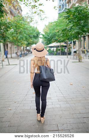 Rear view of city girl walking over pedestrian street enjoying summer stroll. Fashionable summer girl with leather bag travelling over city. Leisure concept
