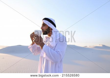 Portrait  confident and happy male Muslim who drinks invigorating coffee drink from white cup and enjoys calm morning, standing in midst of endless sandy desert with pure white sand in open air on warm summer morning. Swarthy Muslim with short dark hair d