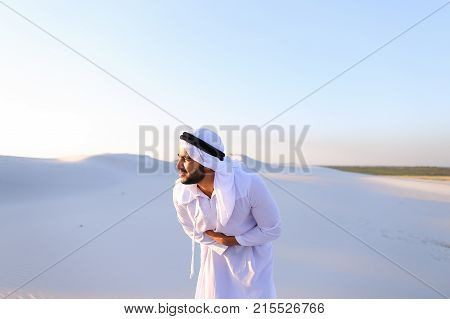 Worn-out Emirati man bends from pain and clings to stomach, suffers from severe pain and suffers with all strength, standing in midst of bottomless desert with snow-white sand on sunny summer day. Swarthy Muslim with short dark hair dressed in kandura, lo