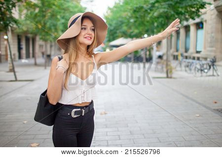 Happy young woman catching taxi outdoors and waving hand. Positive attractive lady in sunhat enjoying city life. Taxi service concept