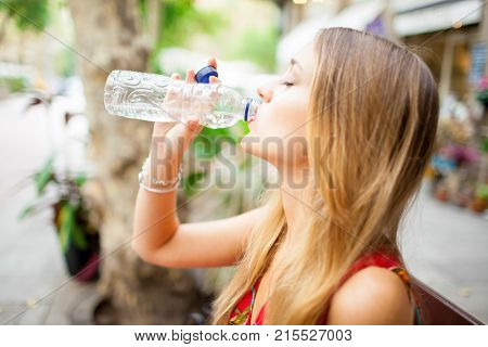 Tired female tourist with closed eyes drinking water outdoors. Calm young woman enjoying refreshing drink during stifling heat. Thirsty concept