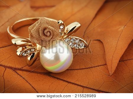 Jewelery ring with pearl on yellow leaves