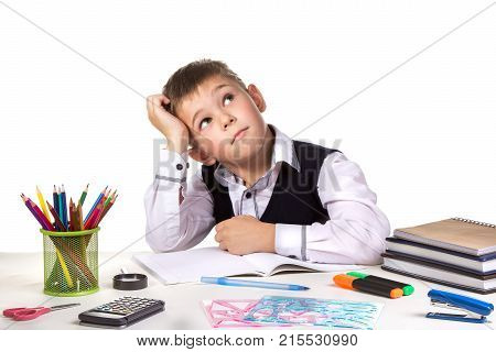 Excellent pupil thinking over the puzzle sitting at the studing desk with white background.