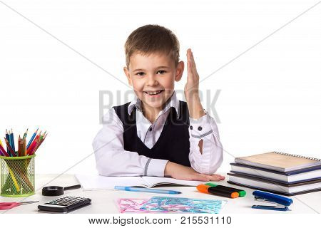 Smiling excellent pupil with hand up sitting at the table on the white background.