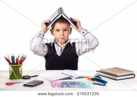 Smart serious excellent pupil at the desk with open book on the head on the white background.