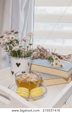 Sweet welcoming home with flowers tea and books is the perfect place for rest. Cozy house concept