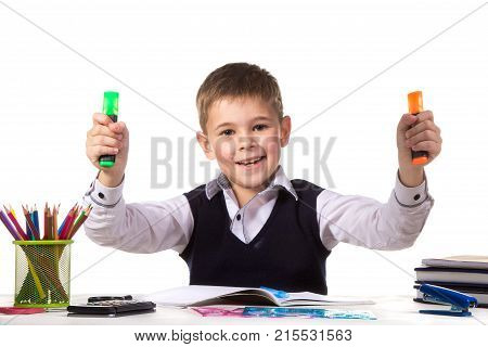 Cheerful pupil sitting at the desk with bright felt-tip pens surrounded with stationery.