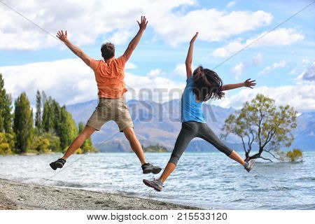 New Zealand tourists couple jumping of happiness at Wanaka Lone . Happy young people doing funny jump of joy sightseeing traveling in summer adventure destination. Woman and man.