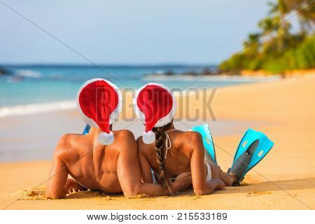 Christmas santa hat holiday couple lying down relaxing on suntan vacation at tropical Caribbean beach. Happy people with snorkel fins for water swim fun.