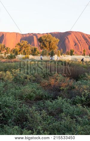 ULURU, AUSTRALIA - OCT 26, 2017: Visitors take a morning walk around Ayers Rock.