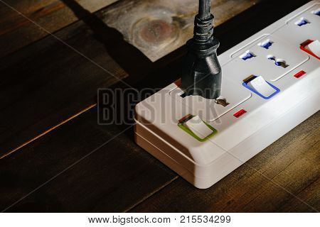 Electrical Plug Connected To A Power Strip Or Extension Block On Wooden Background, Still Life Close