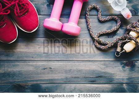 Fitness healthy and active lifestyles love concept dumbbells sport shoes bottle of waters and jump rope in heart shape on wood background. Top view with copy space