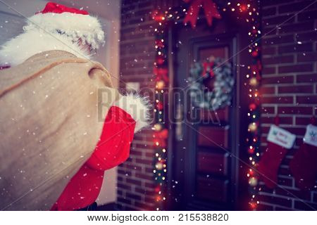 Back of Santa Clause with sack with gifts in front door