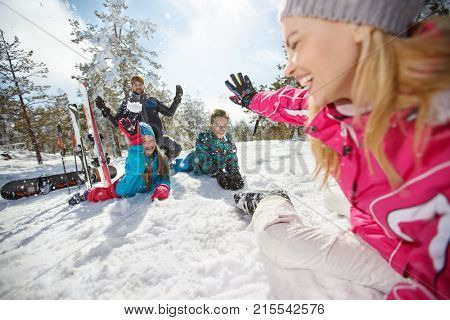 Family on winter holiday making snowballs and having fun