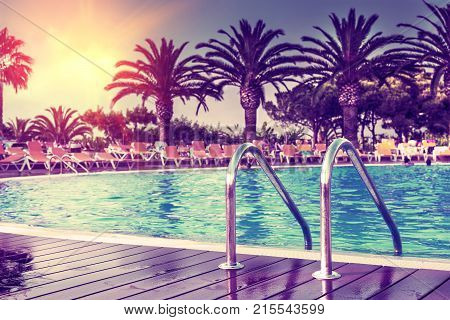 Summer concept exotic pool in the hotel with palm tree.Sunshine and hot days