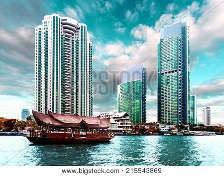 Bangkok city. Skycraper and river Chao phraya. Typical tourist boat