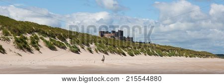 Medieval castle by the sea at Bamburgh Northumberland north east England UK with white sandy beach panoramic view