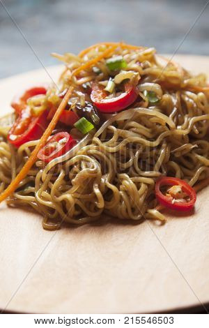 Fried asian instant noodles with bean sprouts, green onion and chili pepper