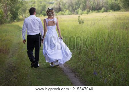 Belarus Gomel July 29 2017.Wedding day.Bride and groom walking along the forest road.Wedding day. The bride before the wedding. Love of man and woman. Lovely couple. Bride and groom.