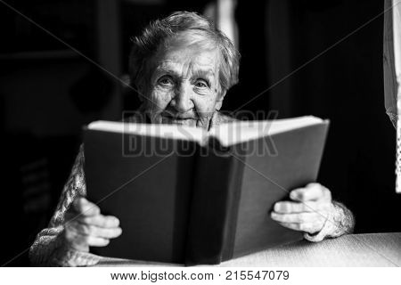 An elderly woman reads the book sitting at the table. Black and white portrait.