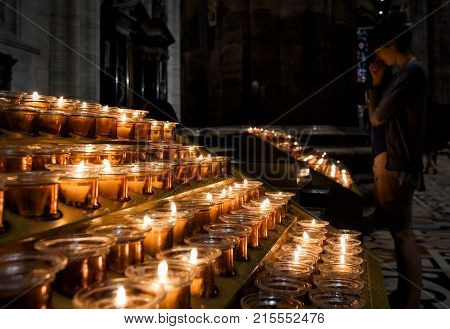 Milan, Italy - May 16, 2017: Candles burn in the Milan Cathedral (Duomo di Milano). Milan Duomo is the largest church in Italy and the fifth largest in the world.