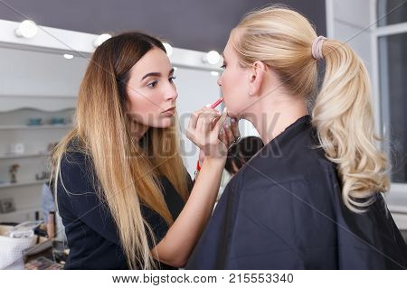 professional makeup artist applying makeup for young woman. Closeup portrait of make up artist at work in her studio. Makeup lips. Backstage photo as visagist doing lip contour with lip pencil
