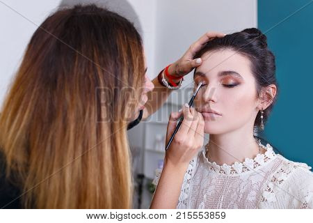 professional makeup artist doing makeup for young woman. Eye makeup. Closeup portrait of make up artist at work in her studio. Backstage photo as visagist applying eyeshadows