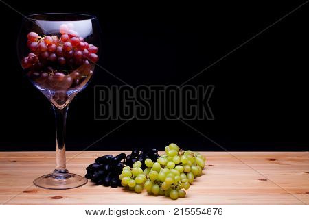Glass of red win grapes. Grape variety still life. Classic painterly image. Red green and black grape varieties. Summer fruit on farmhouse kitchen table.
