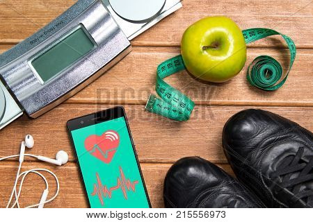 Sports Shoes , Apple , Scales, And A Phone With Health Card On A Wooden Background. Mobile App Healt