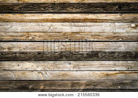 Old weathered brown barn wood wall. Wooden wall background design. Wood planks, boards are old with a beautiful rustic look. Nice studio lighting and elegant vignetting to draw the attention.